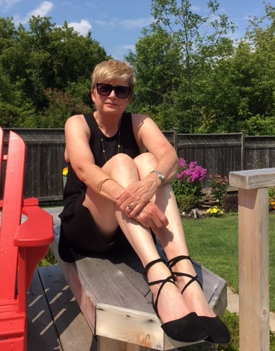 woman in black tank, shorts, and flats sitting on a bench beside a red deck chair