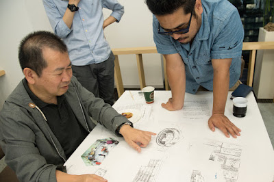 This photo, which accompanied an interview with Yu Suzuki & Katsuhiro Harada, shows Yu with various Shenmue design documents as he points at what appears to be a sketch of a Chinese tulou.