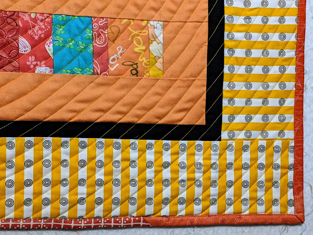 The border and the various orange prints used to bind the quilt are shown.