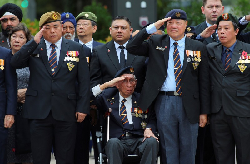 Military veterans salute as Britain's Prince Charles prepares to lay a wreath at the Cenotaph war memorial in Singapore October 31, 2017.