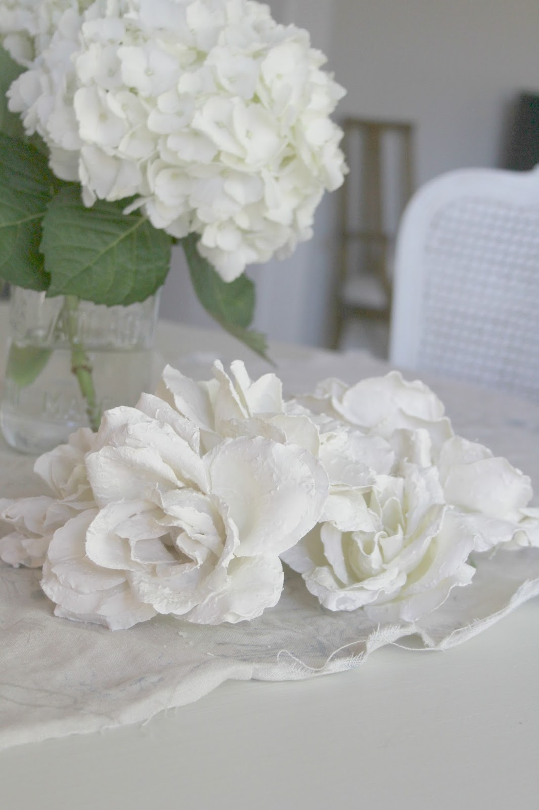 White plaster roses on linen cloth by Hello Lovely Studio