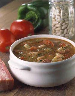 Cuenco con sopa paisana sobre la mesa, acompañado por un trozo de panceta, un morrón verde, dos tomates y un frasco con legumbres
