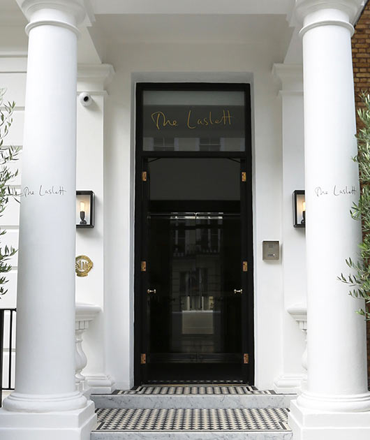 Black front door of The Laslett Hotel in Notting Hill in the heart of West London