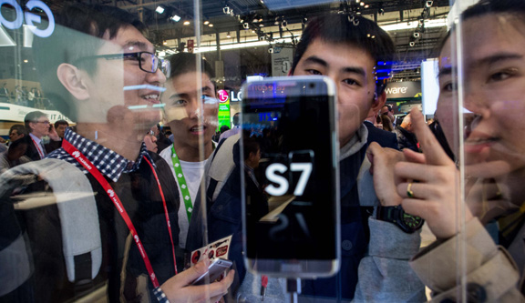Visitors look at the new Samsung Galaxy S7 on the opening day of the World Mobile Congress on Feb. 22, 2016, in Barcelona. PHOTO: DAVID RAMOS, GETTY IMAGES