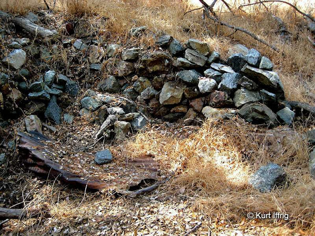 This rock wall was probably part of a miner's camp or cabin, possibly related to a nearby mine.