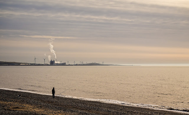 "Photo of a lone fisherman on the shore at Maryport and the ""cloud factory"""