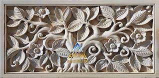 Relief batu putih motif bunga kamboja