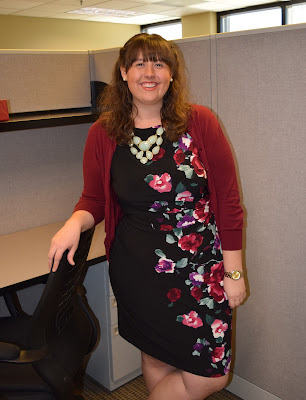 an outfit with a black floral dress, maroon cardigan, and maroon flats