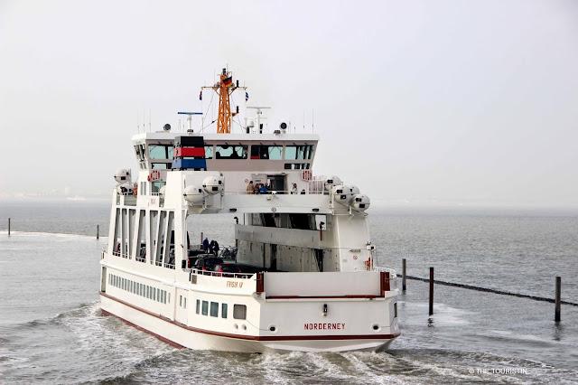 A small white passenger ferry leaving the passenger port.