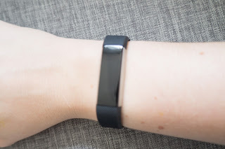 Black Fitbit Alta on wrist.