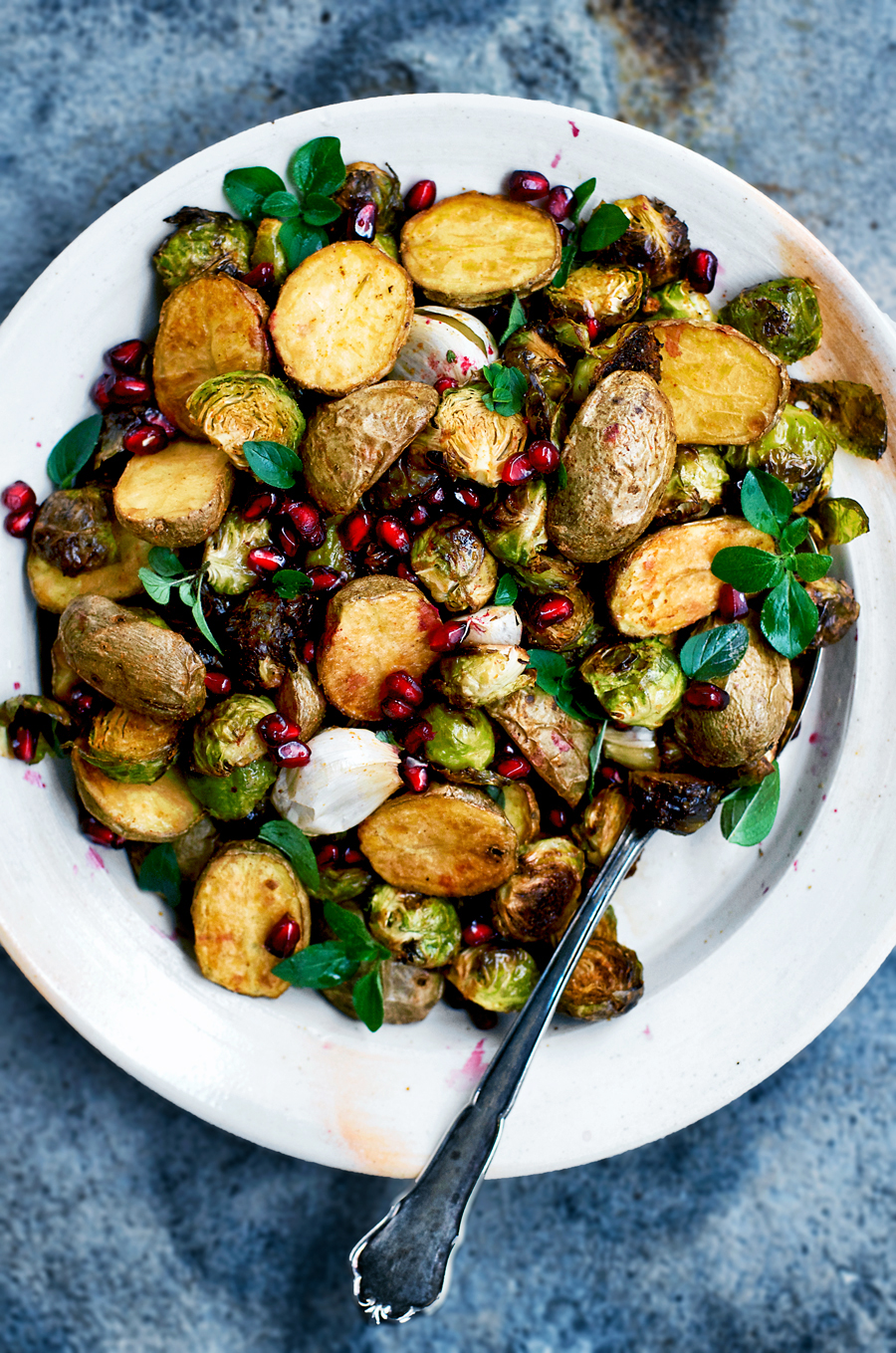 Roasted new potatoes and brussels sprouts, mixed with pomegranate, roasted garlic, and lots of spices, make for a beautiful holiday side dish with festive colours. Meaty brussels sprouts and crispy potatoes combine with bright pops of pomegranate here for a special vegan side.