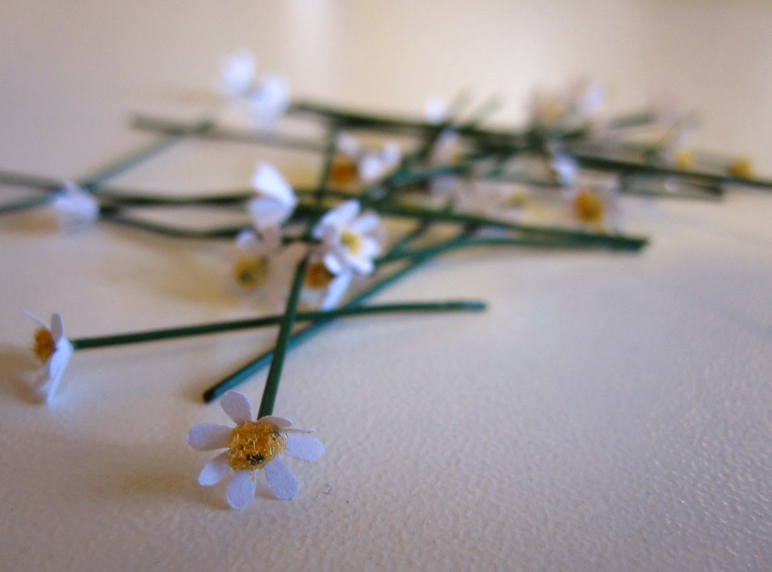 Twenty scattered hand-made miniature daisy flowers stems.