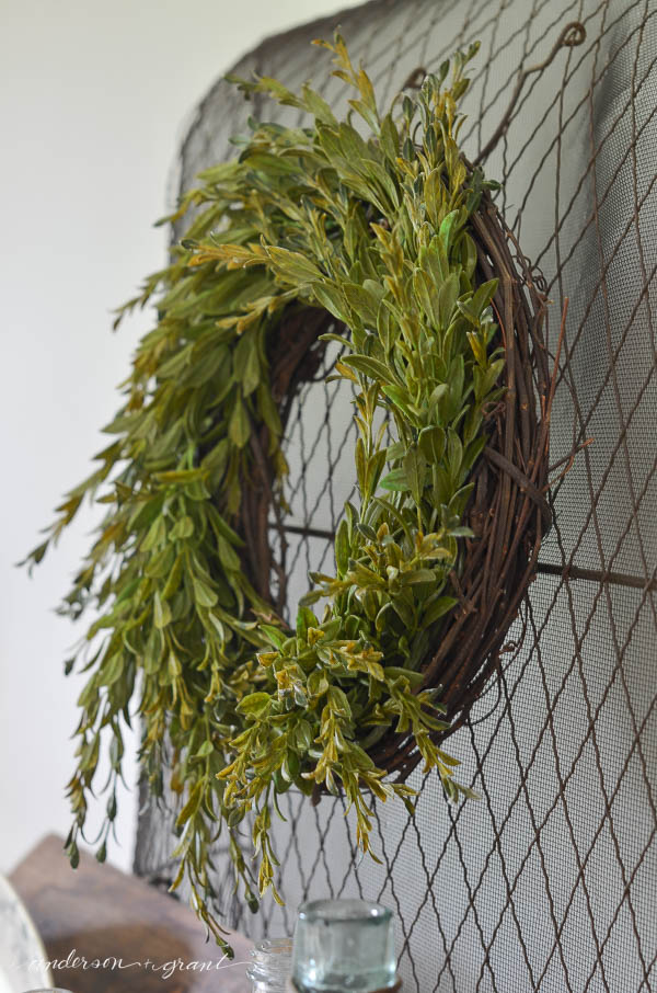 A wreath hanging on the front door says HOME.  Find out how to make this stylish boxwood wreath to brighten up the outside of your house!   |  Tutorial at www.andersonandgrant.com