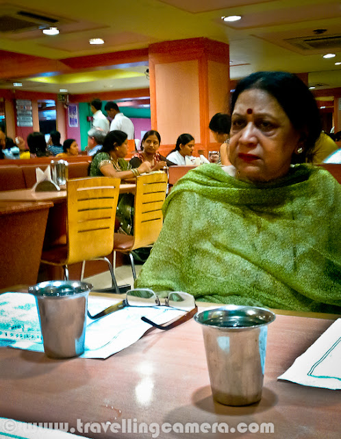 Few days back one of my friend told me about Sarvana Bhavan in Connaught place and we though of having lunch at the same place. It's just opposite to Janpath Market near CP, Delhi. Let's have a quick Photo Journey to Sarvana Bhavan in Connaught Place with some information about it's food and specialties...Welcome to Sarvana Bhavan. As you know, all popular places in Delhi are usually crowded. So the story of our lunch also started with waiting time for 25 minutes. And after a long wait we had to share the table. Since my friend was crazy about the South Indian food here, I simply followed the trends if Sarvana Bhavan. Otherwise I would have spent those 25 mins in locating some other good place which could offer comfortable seating at least.Here is what exactly we saw inside Sarvana Bhavan. Both of the floors were full of people and seating were extremely tight. There was hardly any space between the tables. It seemed that they get lot of customers daily and available real-estate need to be utilized in such a way.Place is fine for young and old age folks, but if someone want to visit the place with children, I would want to warn them. Waiting for 20 minutes at least and then getting into a tight space and get out of the space after finishing your food - This whole cycle will suffocate the kids with you. As there is no place for them to enjoy inside Sarvana Bhavan.Anyway, it was time to look at the menu and decide on items we wanted to have for Lunch. I got the reasoning behind the popularity and spacing problem. Their charges were very nominal. But I was expecting lovely south Indian food at same time. Let's see how it goes...We were sharing our table with this interesting couple, who ordered very unique items in lunch. They took enough time to look at all the items in Menu and then decided to have a special thali and Paper masala Dosa, with salted Dahi-Vada after main meal.Overall place was clean and comfortable, if we forget about the spacing. It's a completely air conditioned restaurant, which serve almost every South Indian Dish. Service was again good, as one person was dedicated for each row, who was only involved for taking order and making sure that no one is waiting for any type of service. Most of them communicate in South Indian Language(s)...We ordered on simple Thali and a Butter Rava Masala Dosa. I failed to notice anything good about the food here. South Indian at Sagar Ratna is far better that Sarvana Bhavan, but not sure why it's name is so popular. If you are reading this post and like Sarvana Bhavan food, please comment back and share about the things you like at this place.When we were waiting for our order to come, uncle and aunti were discussing about Sarvana Bhavan in Lajpat Nagar and they were really impressed by the food there. At the same time uncle received 4-5 calls and informed everyone that he is in CP Sarvana Bhavan with his wife.Here come our simple thali with a  two Masala Dosas, Sambhar, Coconut chutney, one Subzi & some rasam. And yes, Sweet halva was also part of this thali. Food was ok, but not something great or special... Give an option, I will never com back to this place and would love to go to Sagar ratna for real taste of South Indian Food.After having food expressions were really like this. Uncle was really disappointed with food and also gave the same feedback to manager on second floor. Although, Manager's expressions were saying that he was not bothered much about what the gentleman explained to him.Sarvana Bhavan is good for one time experience and then decide yourself :)