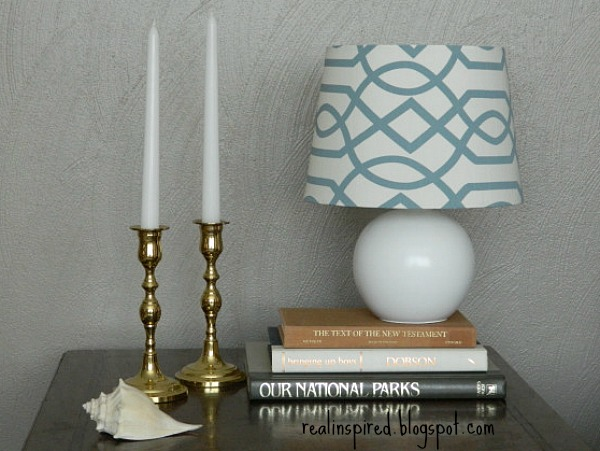 An easy DIY tutorial for how (NOT) to paint a ceramic lamp. This lamp was completely transformed with some spray paint and a new lampshade then styled with brass candlesticks and books.
