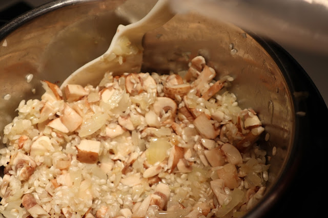 Adding rice and mushrooms to the sauteed onions and garlic.