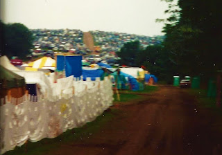 Thousands of cars parked on a hill with many tents closer in front.