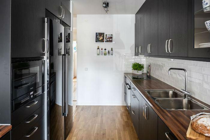 Cocina con mobiliario de madera oscura y encimera de madera. Frente de ladrillo tipo metro blanco.