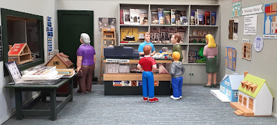 One-twelfth scale miniature dolls' house shop interior, with various people browsing the tiny dolls houses and books.