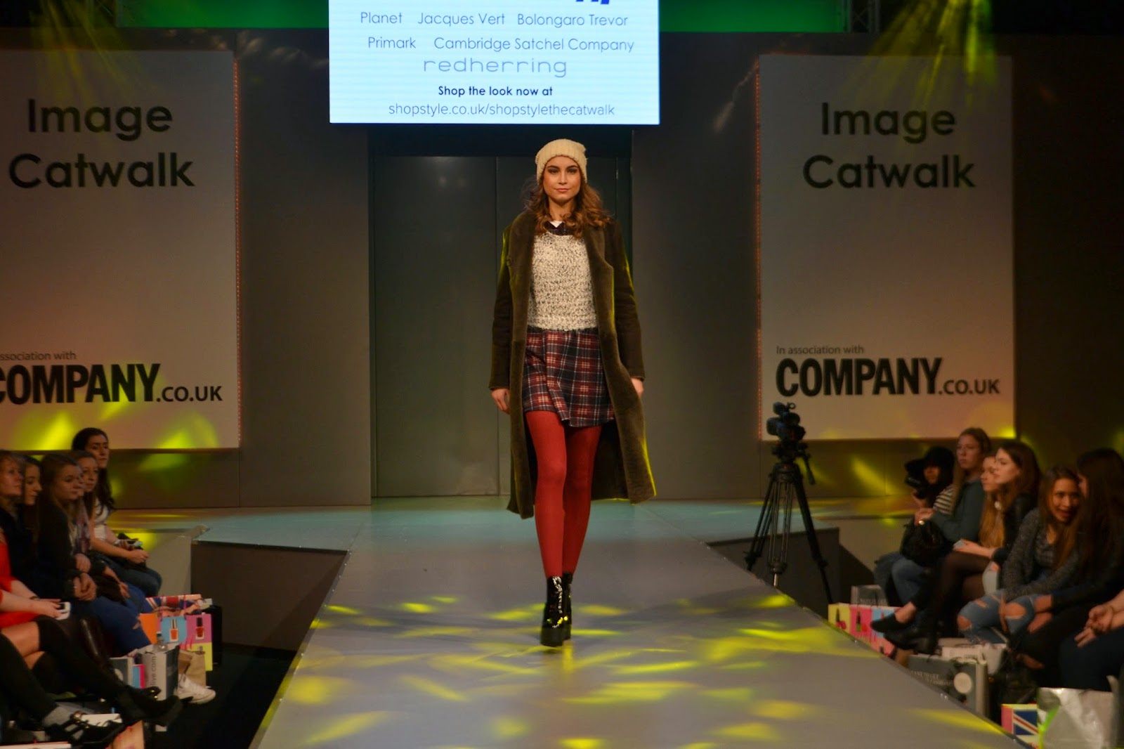 single model walking down the runway wearing red tights, a checked red skirt, a creme jumper, a long green coat and a cream wooly hat