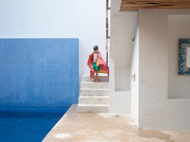 Niño bajando unas escaleras junto a una piscina