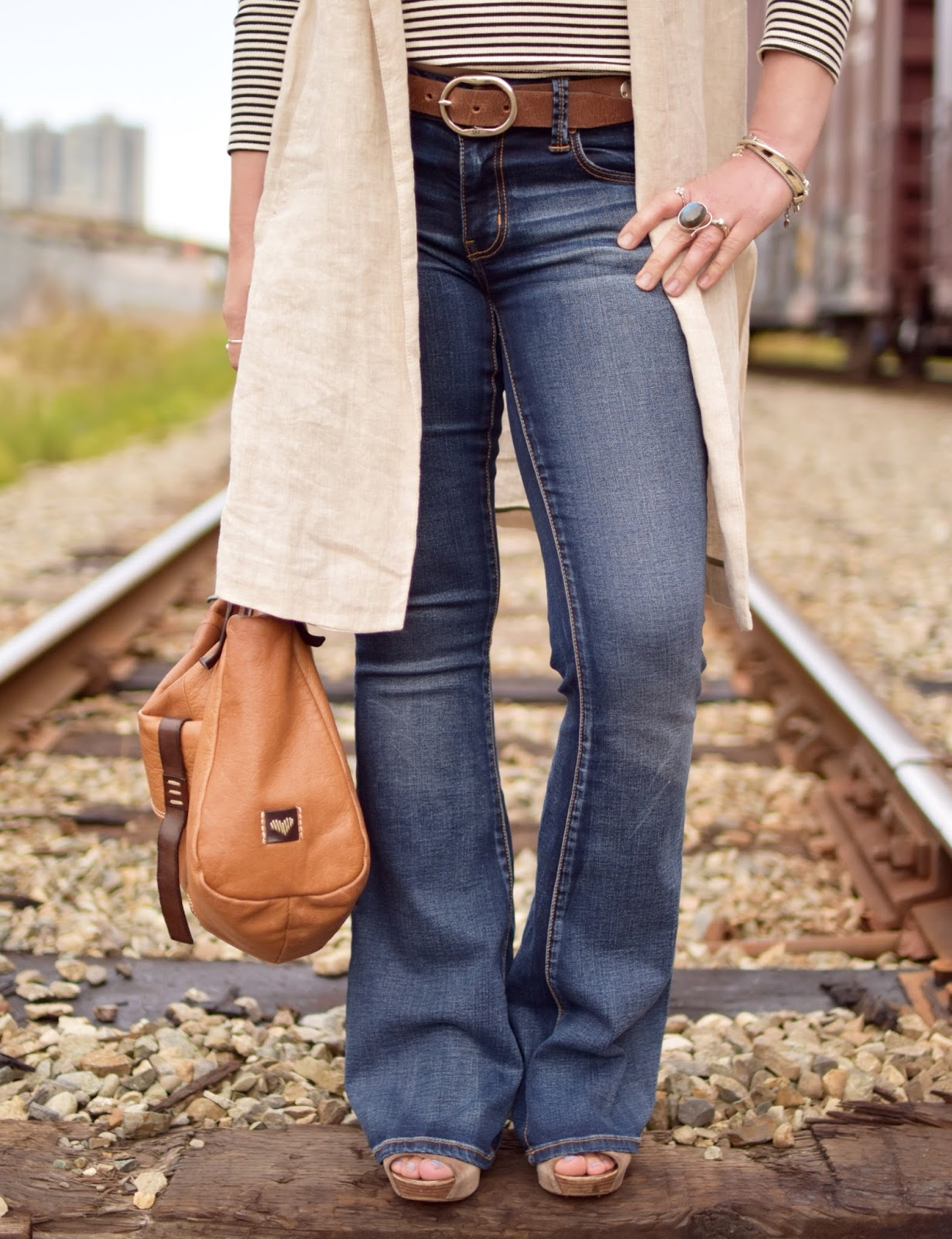 flare jeans, sleeveless linen coat, cognac satchel