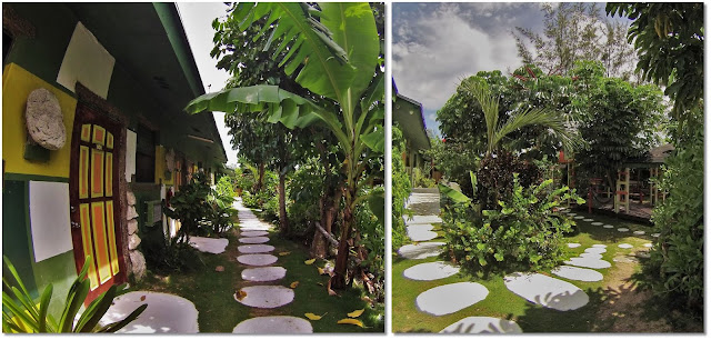 Large stone path leads you through greenery to brightly colored hotel room doors.