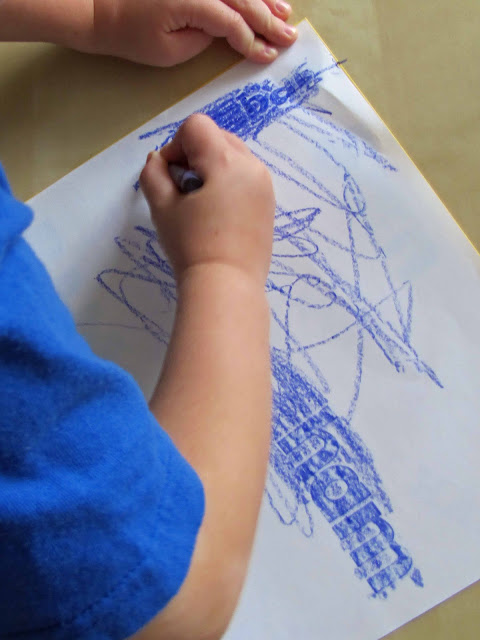 Easy Sight Words Activity by coloring over stickers to spell out words with blue crayons on white paper.