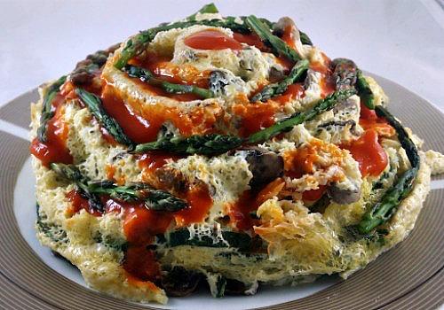 Pastel colorido de verduras adornado con puntas de espárragos y salsa de tomate