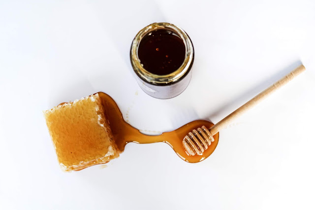 Overlay of honeycomb, honey dropper and jar of honey