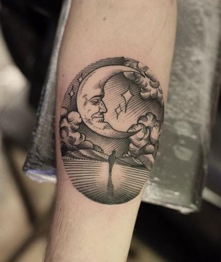 Uma silhueta de uma pessoa olha para cima em uma personificação da lua crescente em preto e cinza tatuagem.