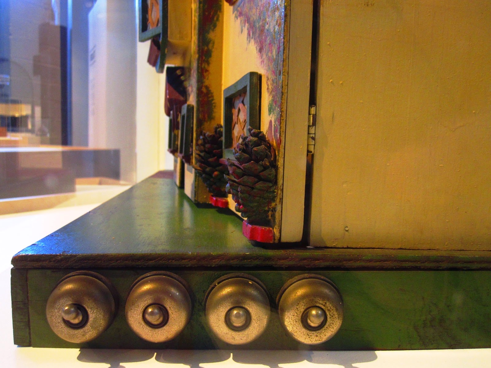 Side view of a vintage doll's house, showing a row of four light switches mounted on the base.