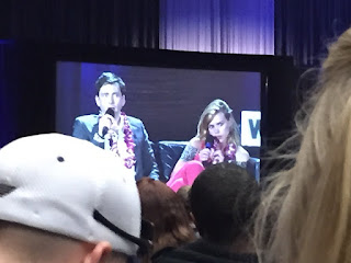 Photo past heads of a giant screen showing David Tennant and Billie Piper on stage.