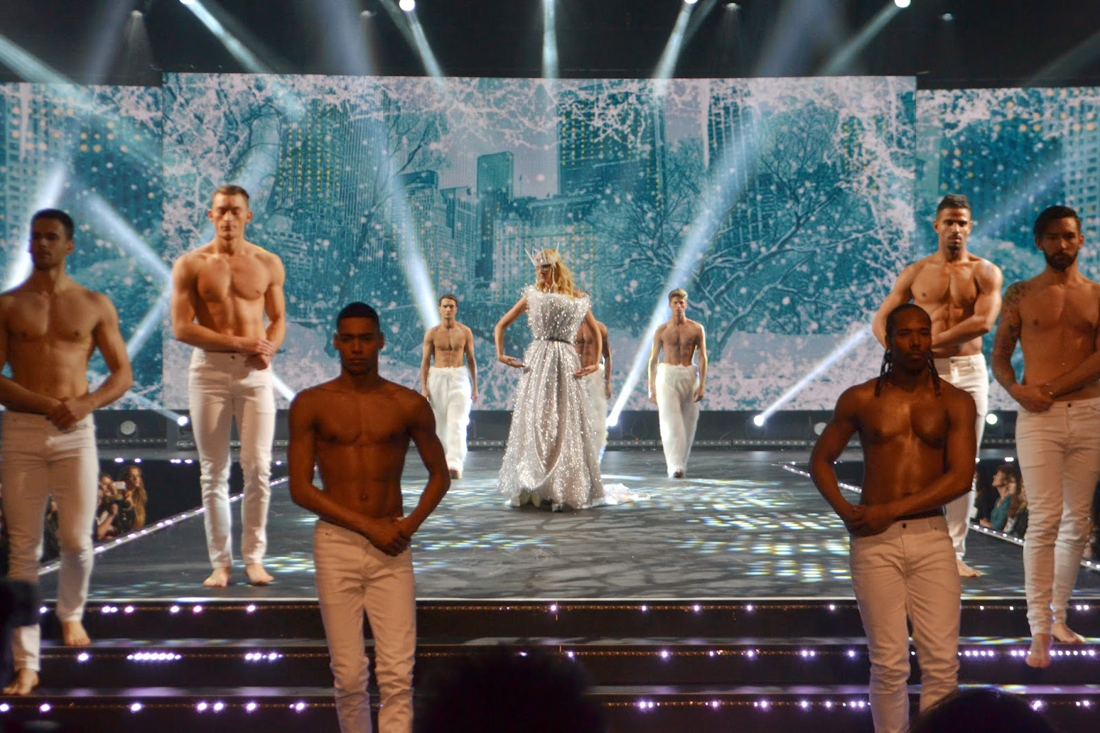 Multiple male and female models walking across the winter themed stage