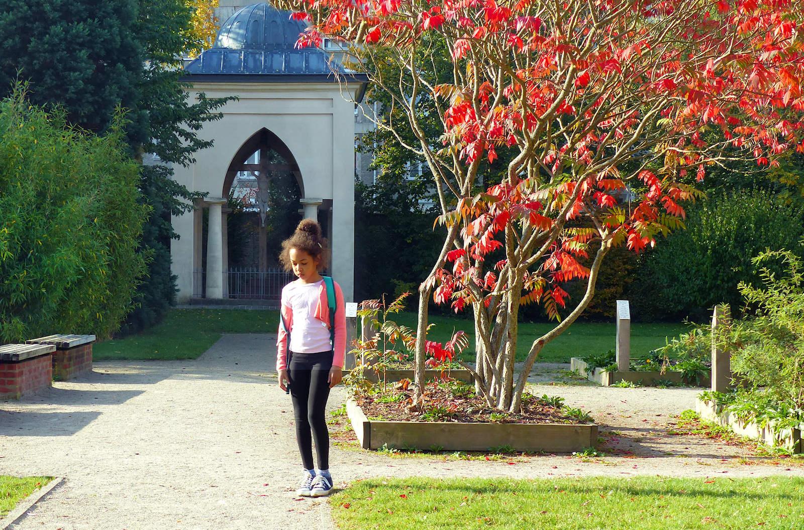Promeneuse dans le jardin, devant le calvaire