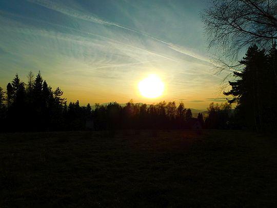 Słońce uderzające blaskiem w twarz zbliża się do górskiego horyzontu.
