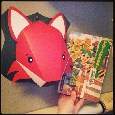 A pale hand holds a paperback copy of the first volume of Yotsuba&! up beside a large, folded paper fox's head. The cover features a small, green-haired girl clutching an armfull of sunflowers taller than she is. The fox's head is stylized in orange and white.