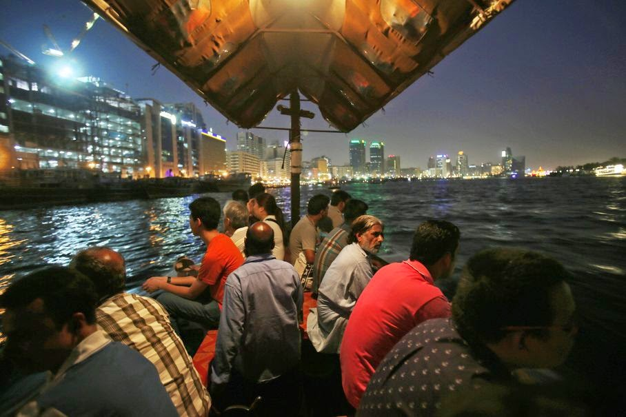 In this Monday, May 26, 2014 photo, tourists and residents cross the creek waters which cuts through the heart of the city, on a traditional abra, or taxi boat, in Dubai, United Arab Emirates. From early morning to late evening the creek is abuzz with daily commuters and tourists riding in abras, the wooden boats that have been used for more than a century and are still built by hand nearby. The 25-cent passage from one bank to the other is one of the only bargains left in a city where much of the population is expatriates lured to the Gulf emirate by job opportunities.