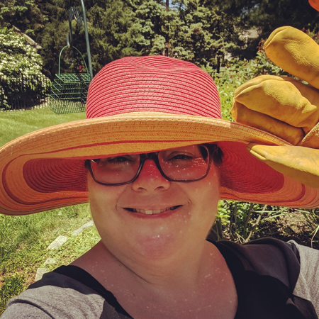 image of me standing in my garden from the shoulders up, wearing grey-framed glasses, a black and grey t-shirt, and a bright yellow and pinky-orange straw hat, the brim of which I'm lifting with my hand clad in a yellow gardening glove