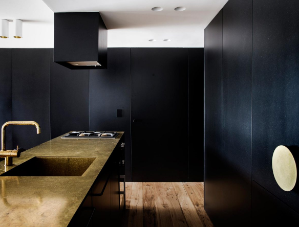 The use of black is offset by brass and mirror finishes that further enhance the sense of ambiguity.