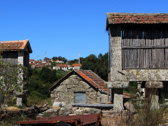 Casa de pedra ladeada por espigueiros
