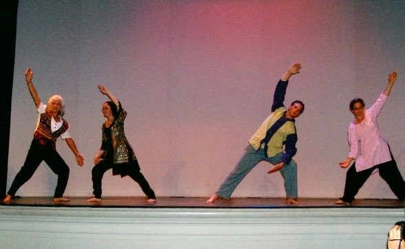 Four people in yogic poses on a stage