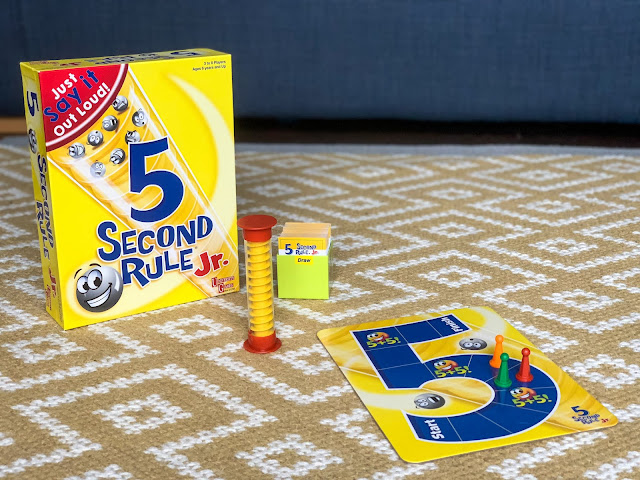 The box contents of 5 seconds rule jr: a game board, games pieces, a timer and playing cards