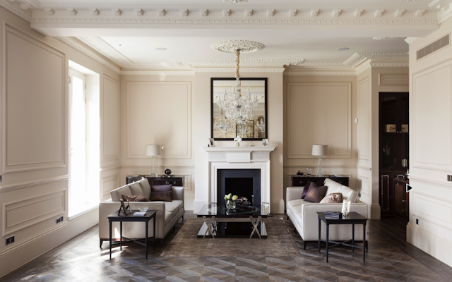 Living room in a suburban London home with carved crown moulding, ceiling medallions, parquet wood floors, decorative wall moulding and paneling and dueling sofas