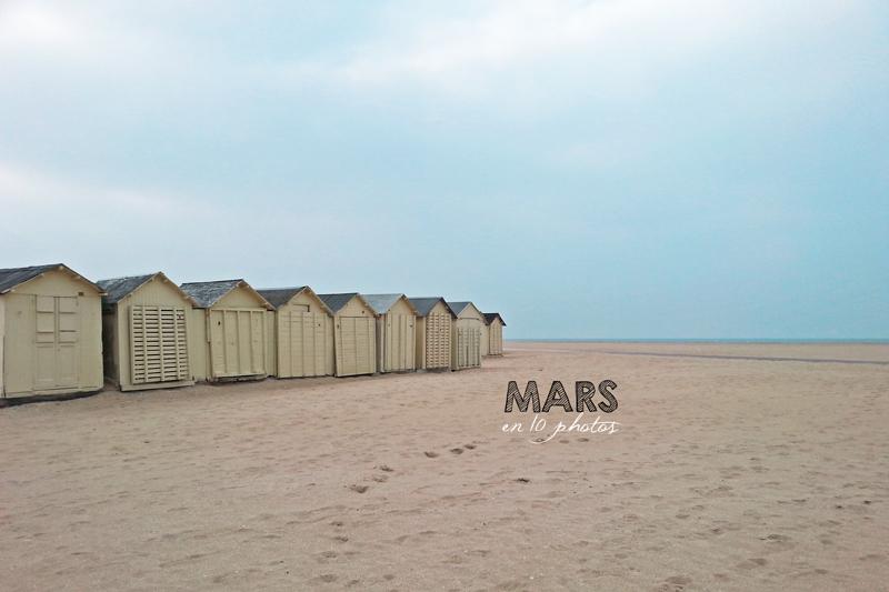 La plage de Ouistreham est vide. Le ciel est voilé et on aperçoit les cabanes de plage.