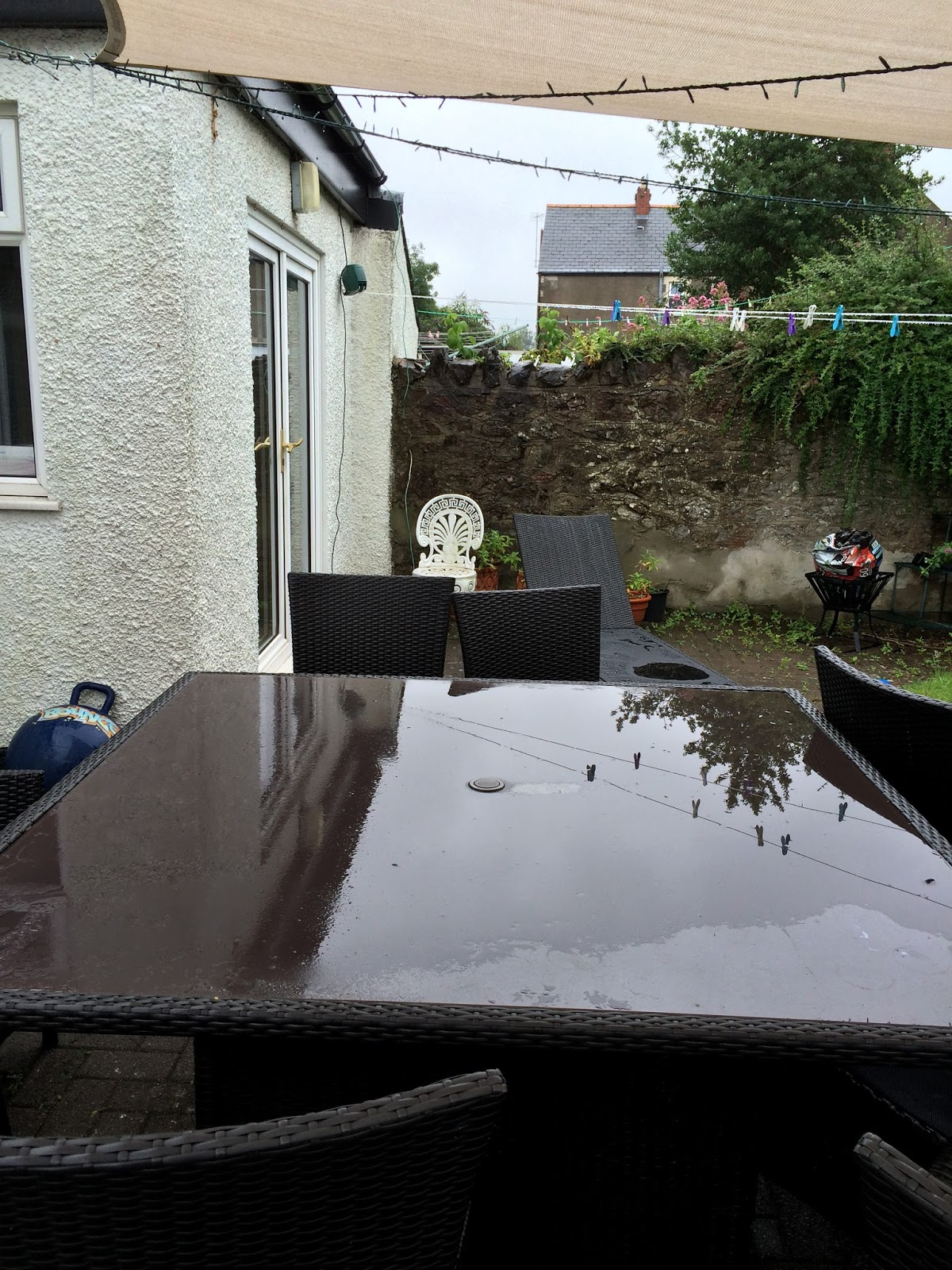garden clean up - garden table and chairs under a shade sail
