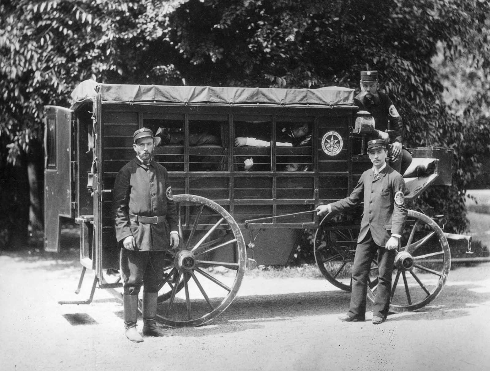 """Una ambulancia de Wiener con pacientes en """"capas"""" en un carruaje de madera tirado por caballos. Los laterales están parcialmente abiertos, pero tienen cortinas. Los ambulancias son miembros de la Sociedad de Rescate Voluntario de Viena, fundada en 1881."""