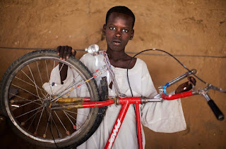 Hamza Ahmad Mohamed is in the Abu Shouk camp for Internally Displaced People, North Darfur, Sudan with his bicycle.