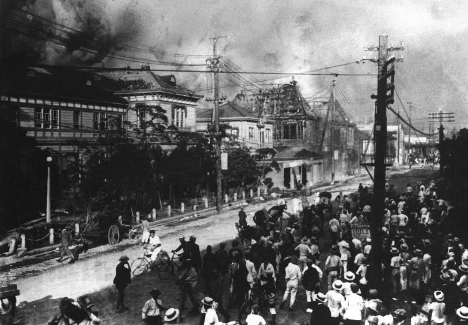 People take refuge on a Nihonbashi street in Japan in 1923. Buildings across the streets are burning and billowing smoke and flame from an earthquake that hit.