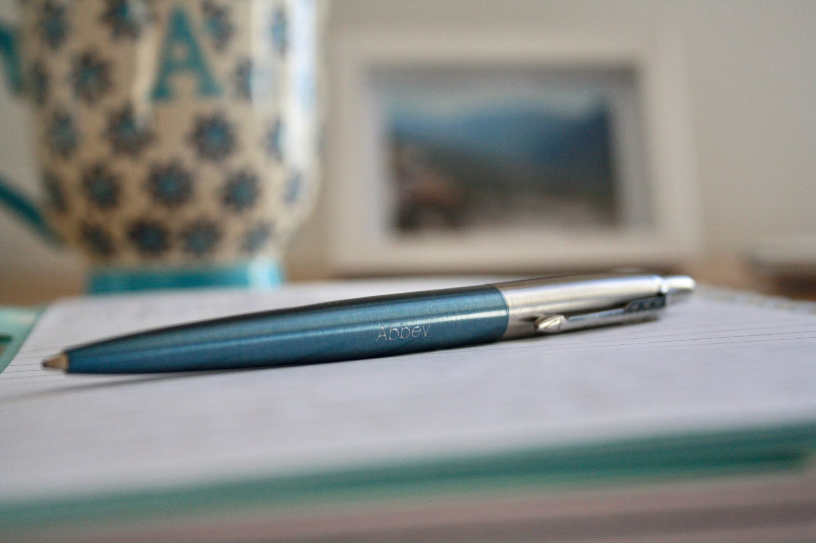 close up of pen resting on open notebook with mug and lamp in background
